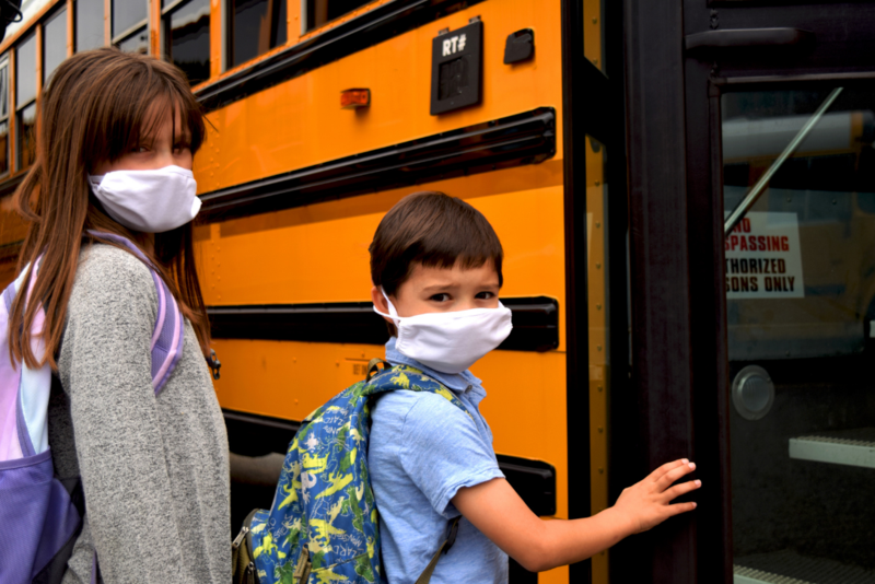 two kids with masks getting on bus