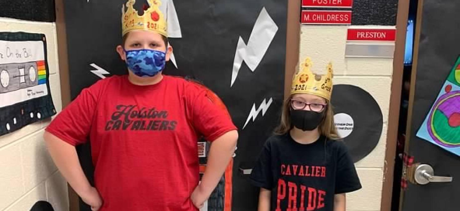 Two students wear crowns in front of decorated doors.