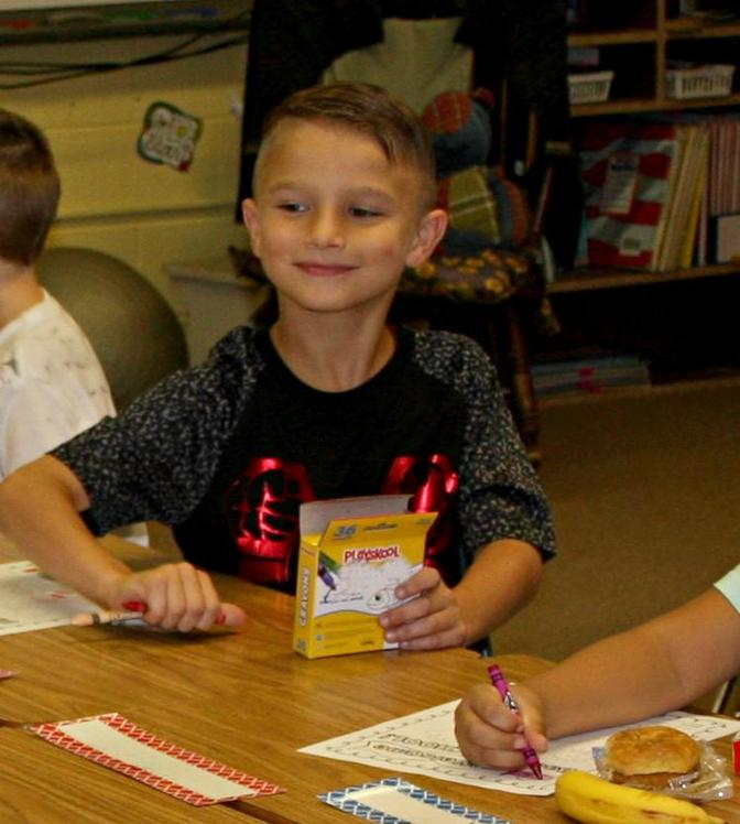 Student smiles at desk while working on the first day of school at C.B. Eller Elementary.