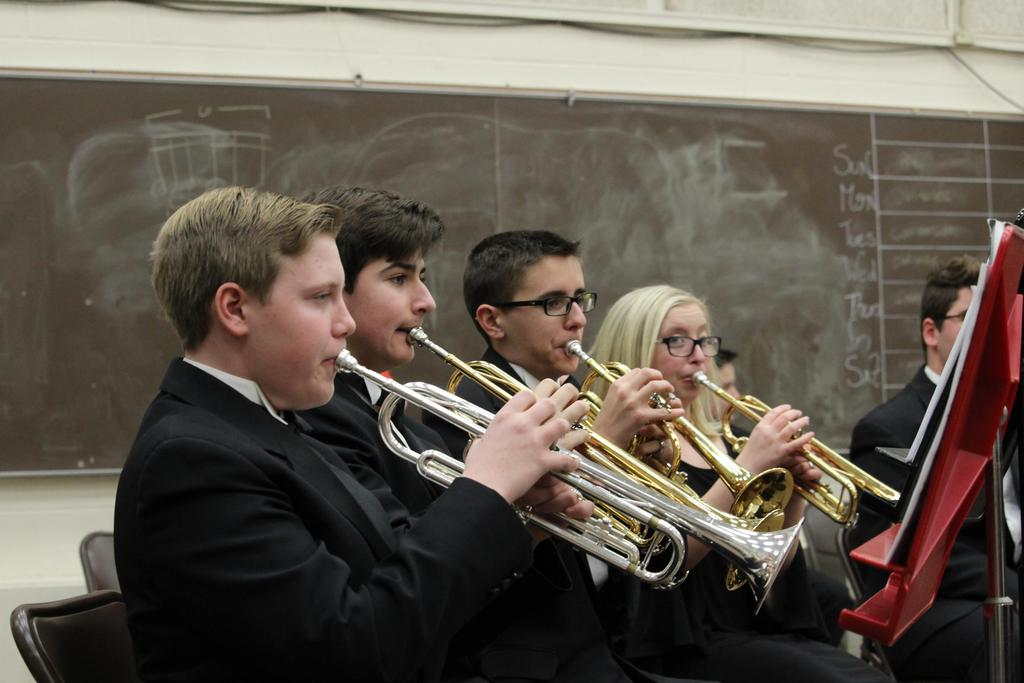 Four students playing trumpets