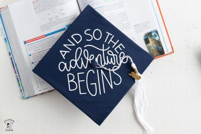grad cap with words and a textbook