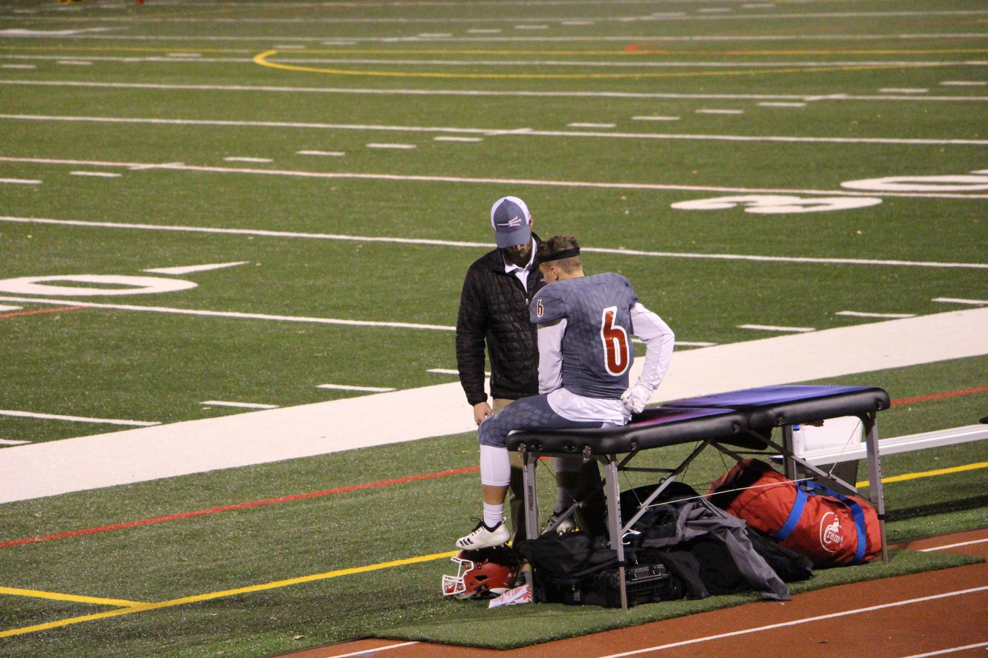 Football player being evaluated on side line