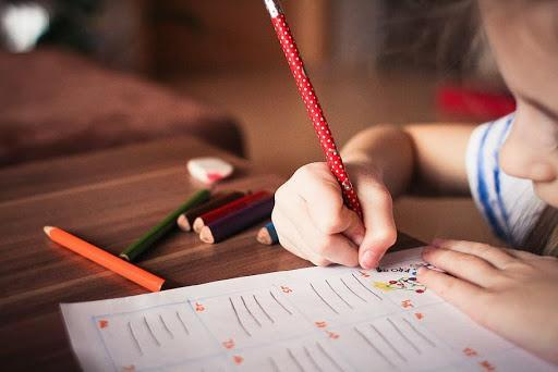 Child writing on desk