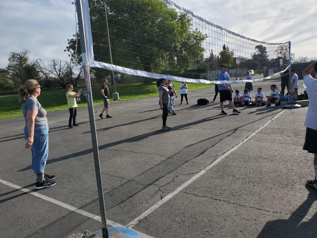 A photo of teachers playing volleyball by a volleyball net.