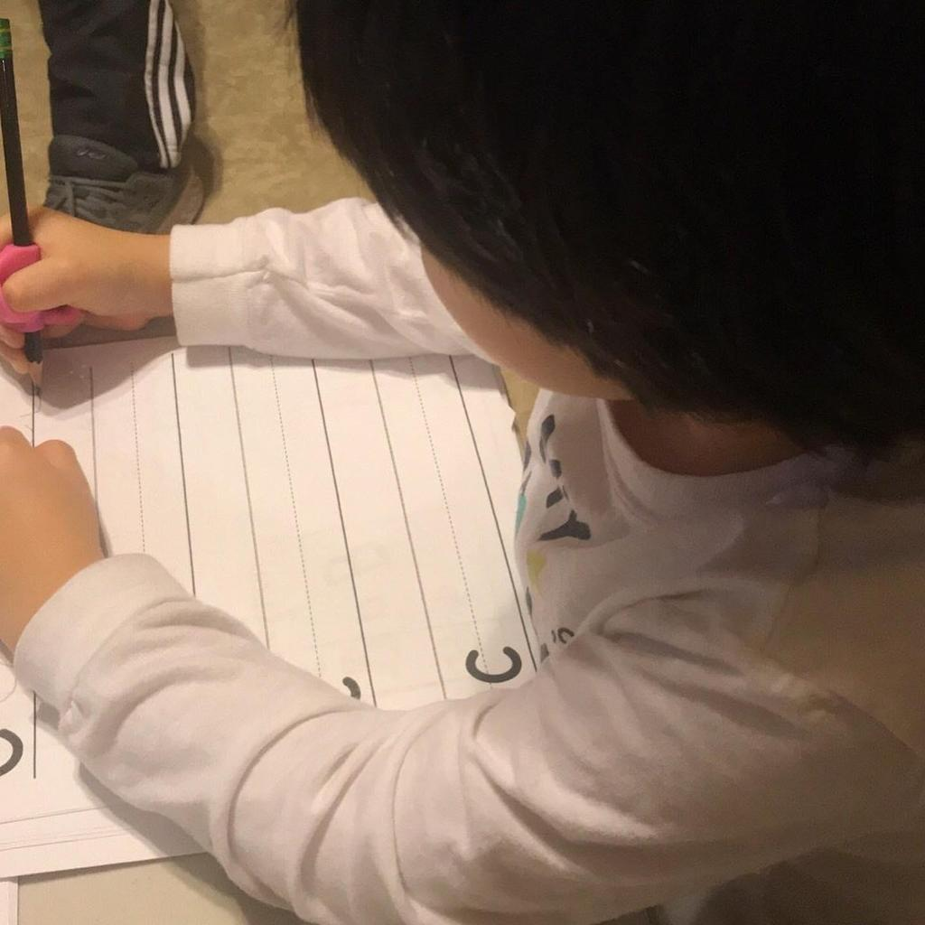 close up of the little boy writing the letter c