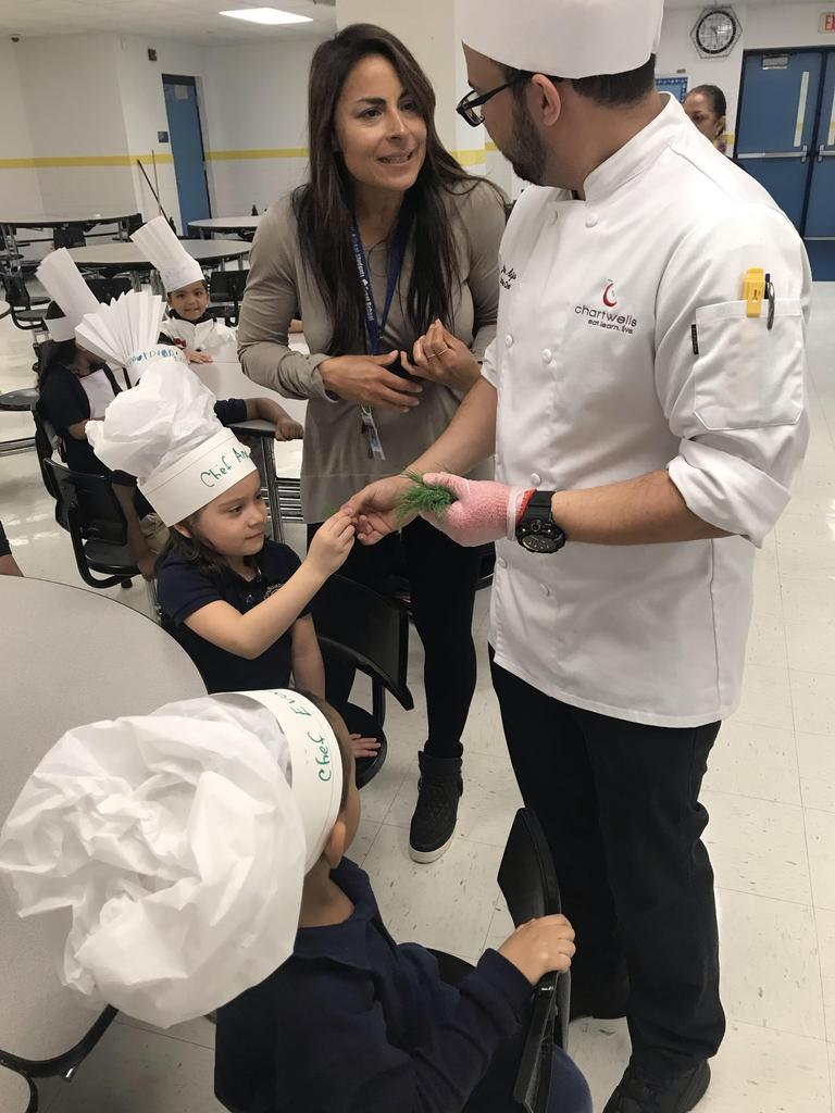 Chef Josh with teacher handing out dill weed for students to taste