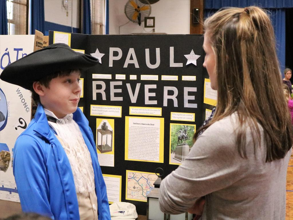 "Photo of Wilson 5th grader dressed as Paul Revere talking to staff member during annual ""Wax Museum"" event."