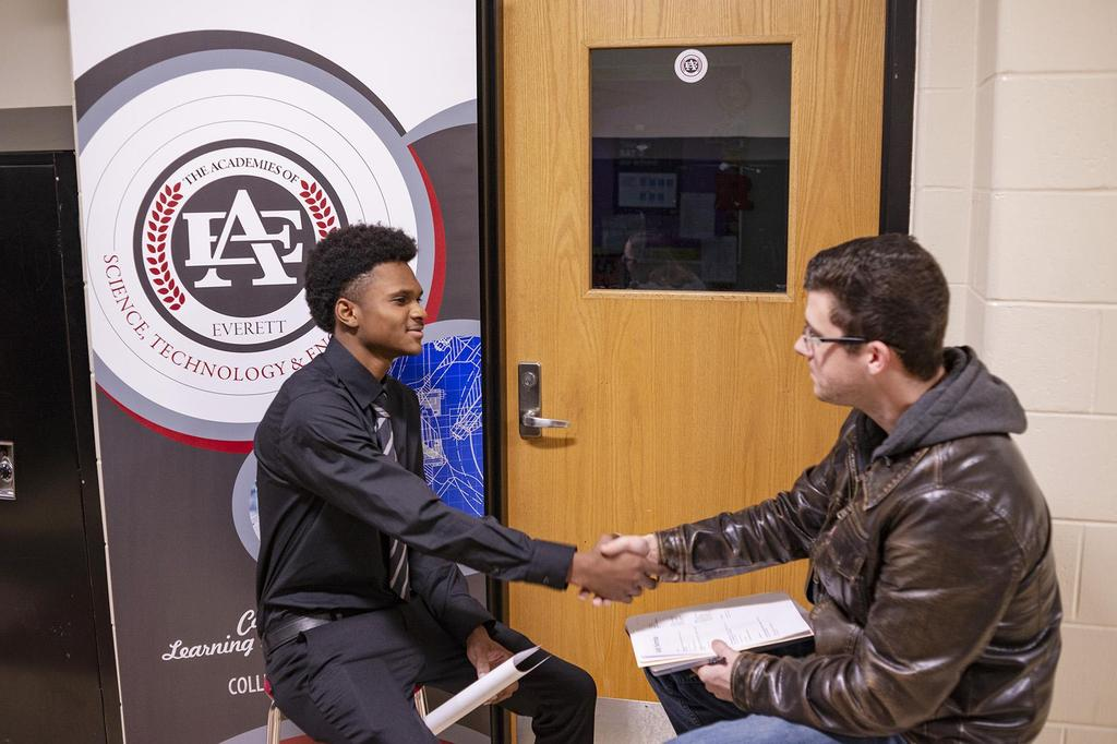 A student shakes hand with an interviewer