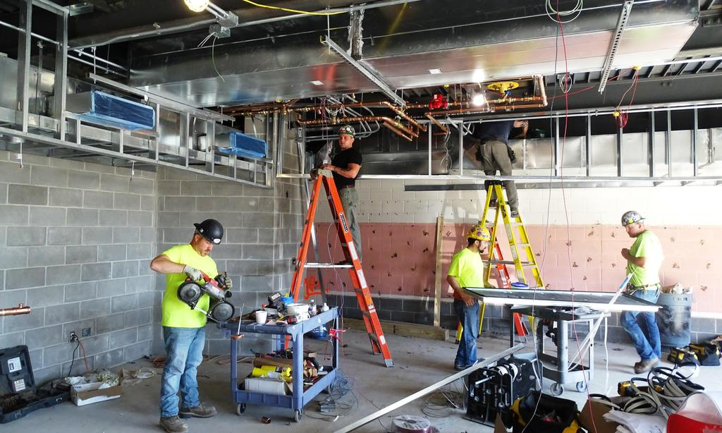 This snapshot illustrates electrical workers and HVAC workers working simultaneously within the Beekmantown Elementary School cafeteria job site, August 23, 2019.