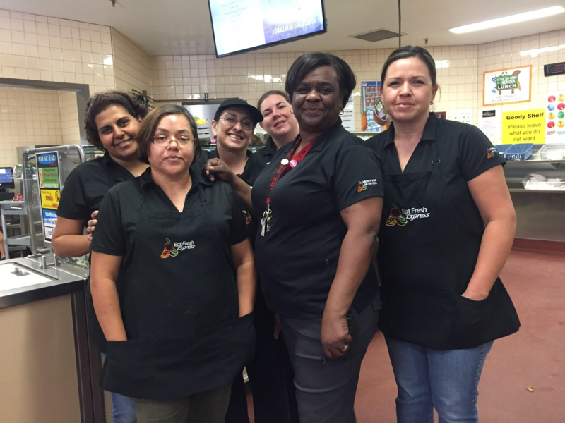 Adriane McCoy-Wilson, Kathleen Banta, Maria Chavez, Doaa Hanna, Anita Olson, and Isabel Bolanos in the kitchen working.