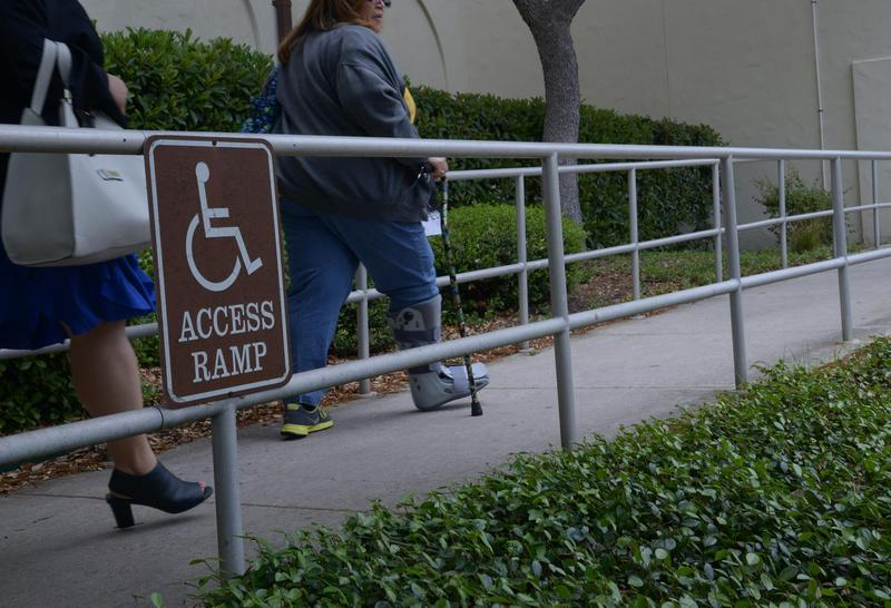 two people walking up a wheelchair accessible ramp