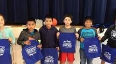 Students posing for the camera while holding their athletic awards.