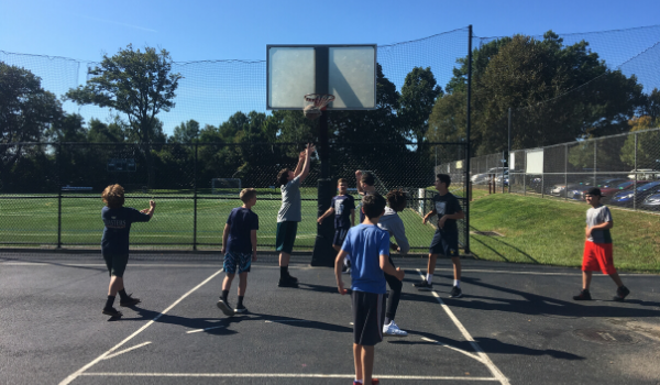 Students play basketball outside during community time.
