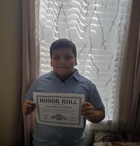 Josue holding honor roll certificate