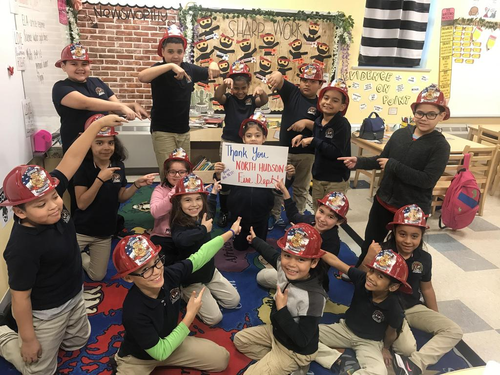 class wearing red fire hats all pointing to a sign thanking the firemen for the visit