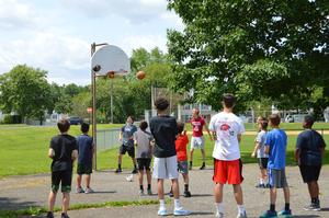 Group of 6th and 10th graders playing basketball on an outside court