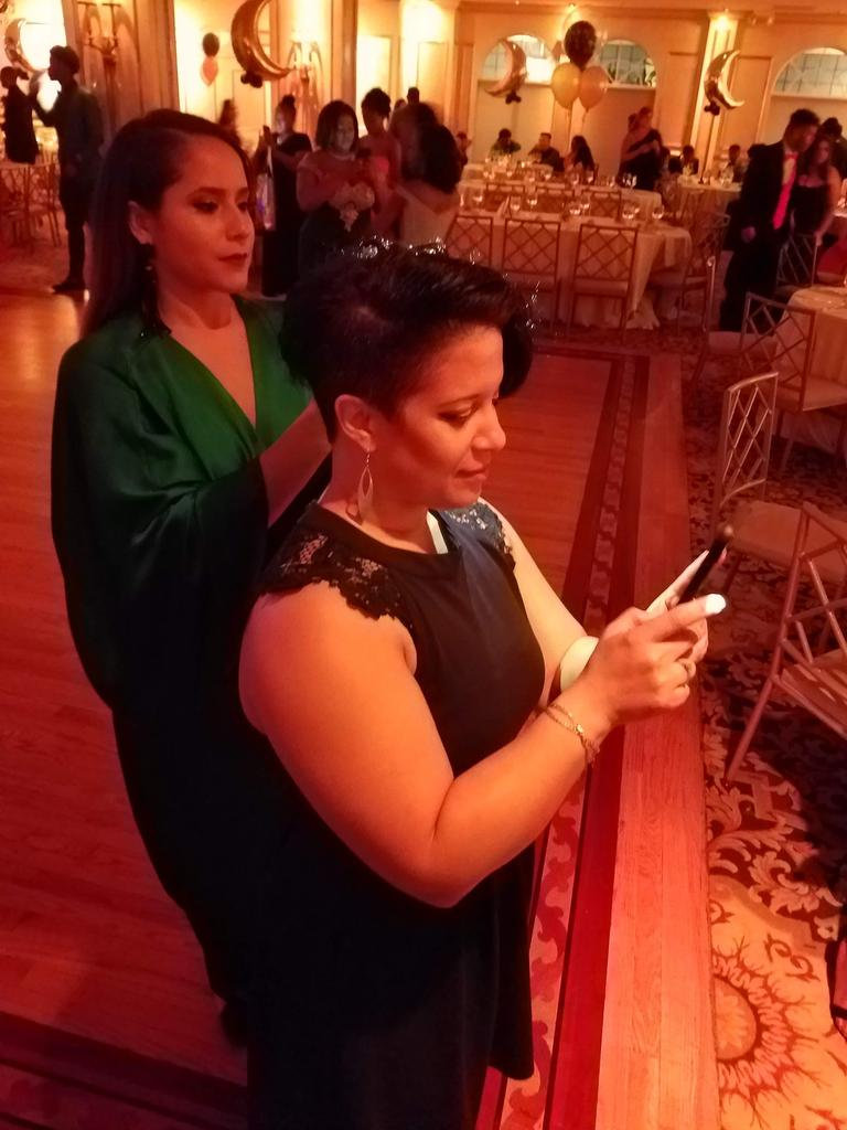 two teachers taking photos with their phones