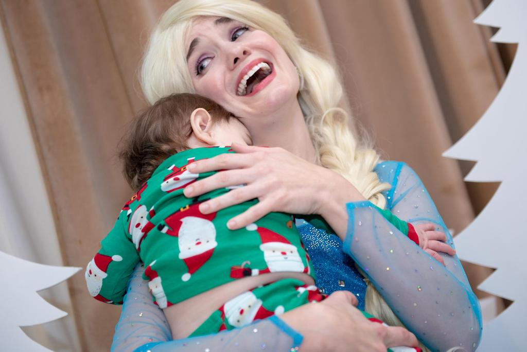 """Elsa from """"Frozen"""" holds a baby"""