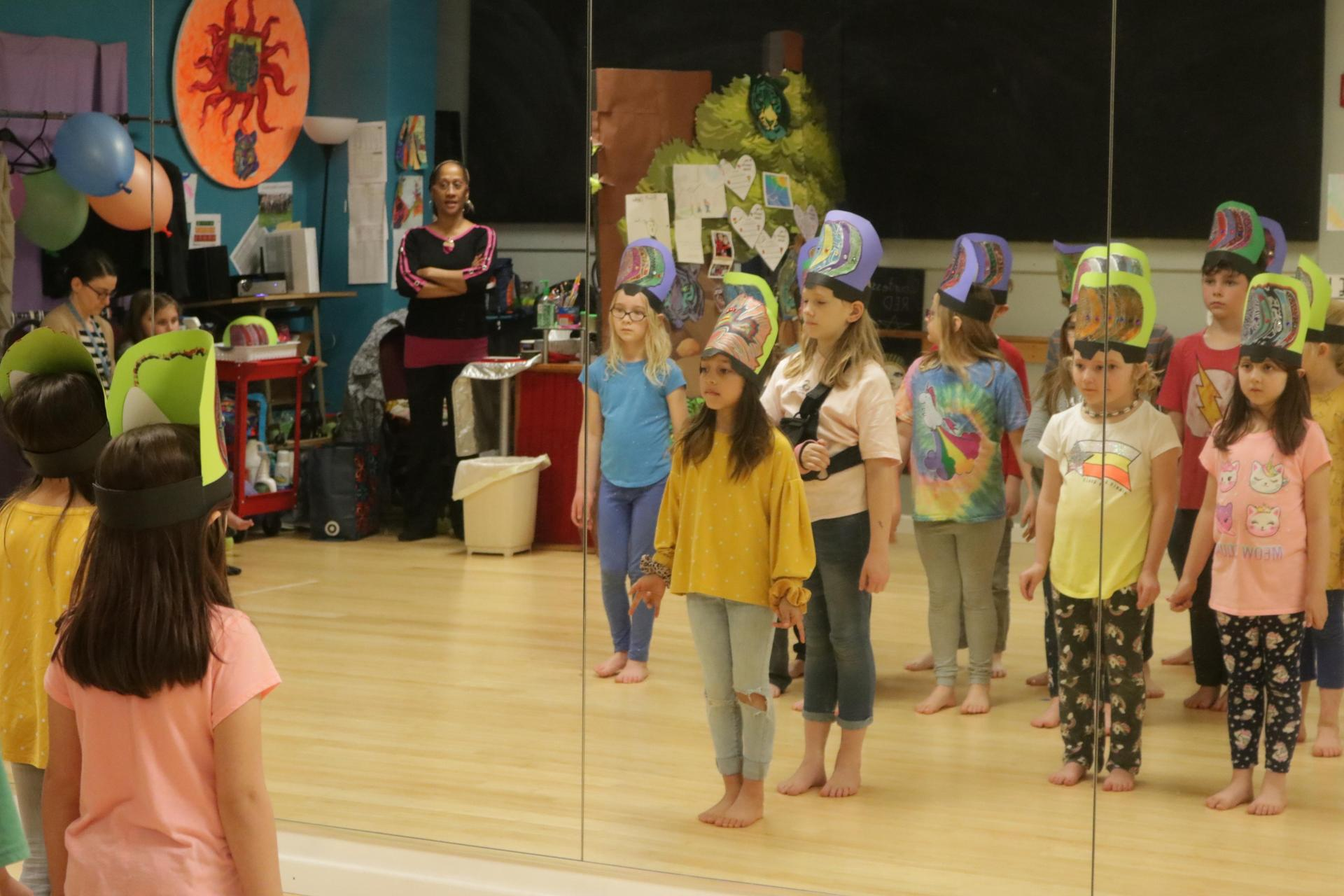 Third graders wear hats and wait for instruction in the dance room