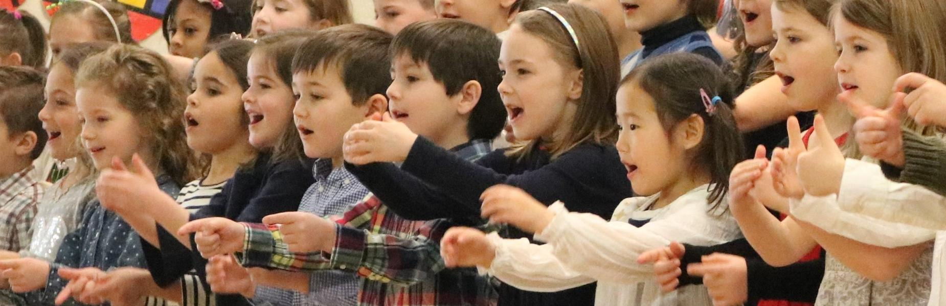 Photo of kindergartners at Lincoln School singing to their grandparents gathered for a special performance.