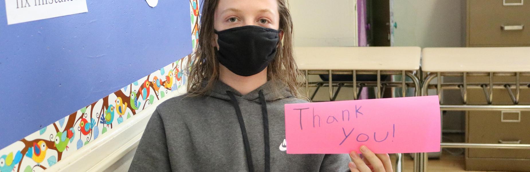 Photo of 8th grader holding handmade card saying