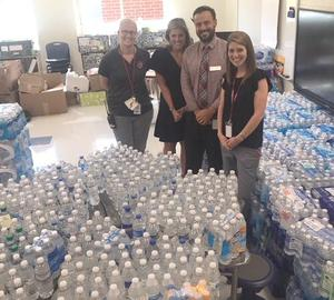 From left, Assistant Principals Elaine Lundy and Allyson Stoy-Long, Principal Andrew Drozdak and Assistant Principal Annette Ariail pose in front of some of the 10,000-plus water bottles collected.