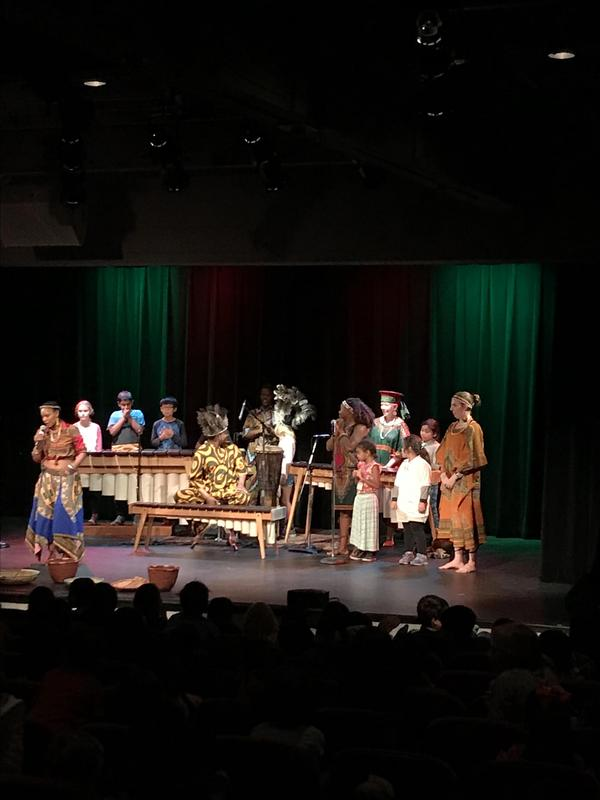 kids on stage, in costume, playing with instruments