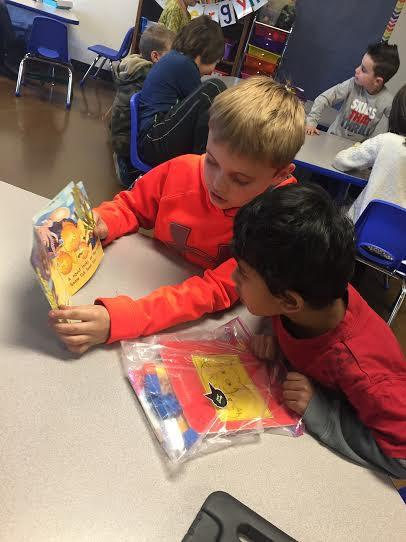 Two young students reading a book together