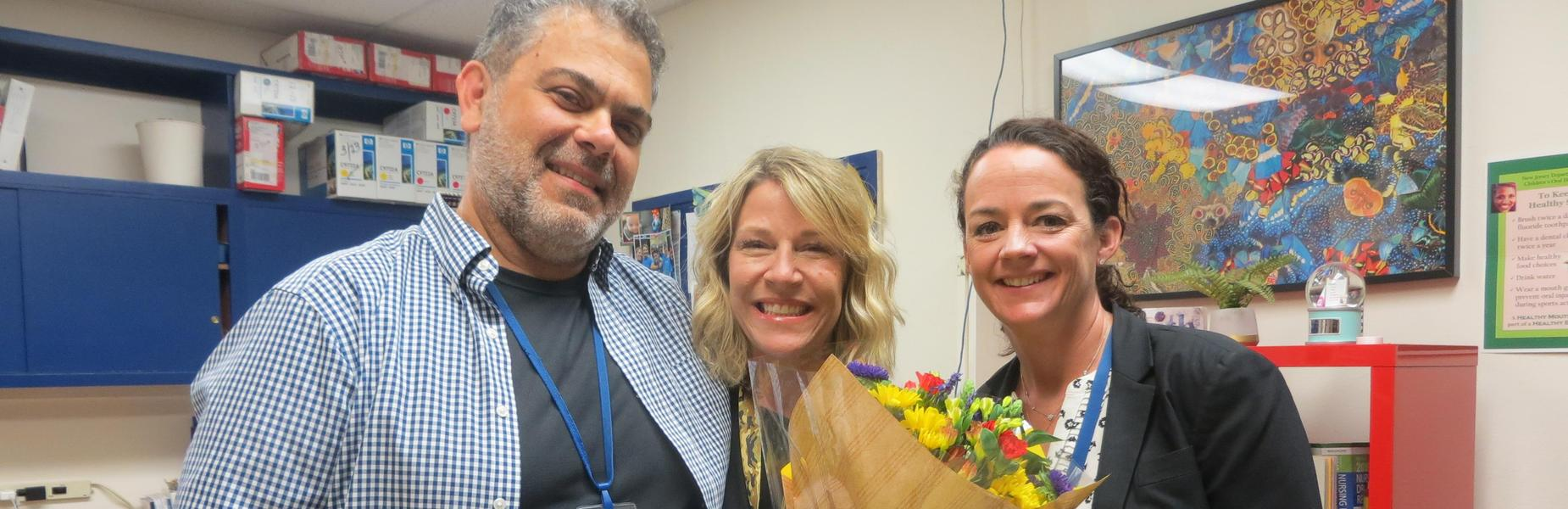 Photo of Roosevelt Intermediate School nurse Sharon Dorry as she learns the news that she is this year's Optimist Award winner for outstanding intermediate school educator.  Pictured here with last year's winner Dominick Ceccio and RIS principal Mary Asfendis.