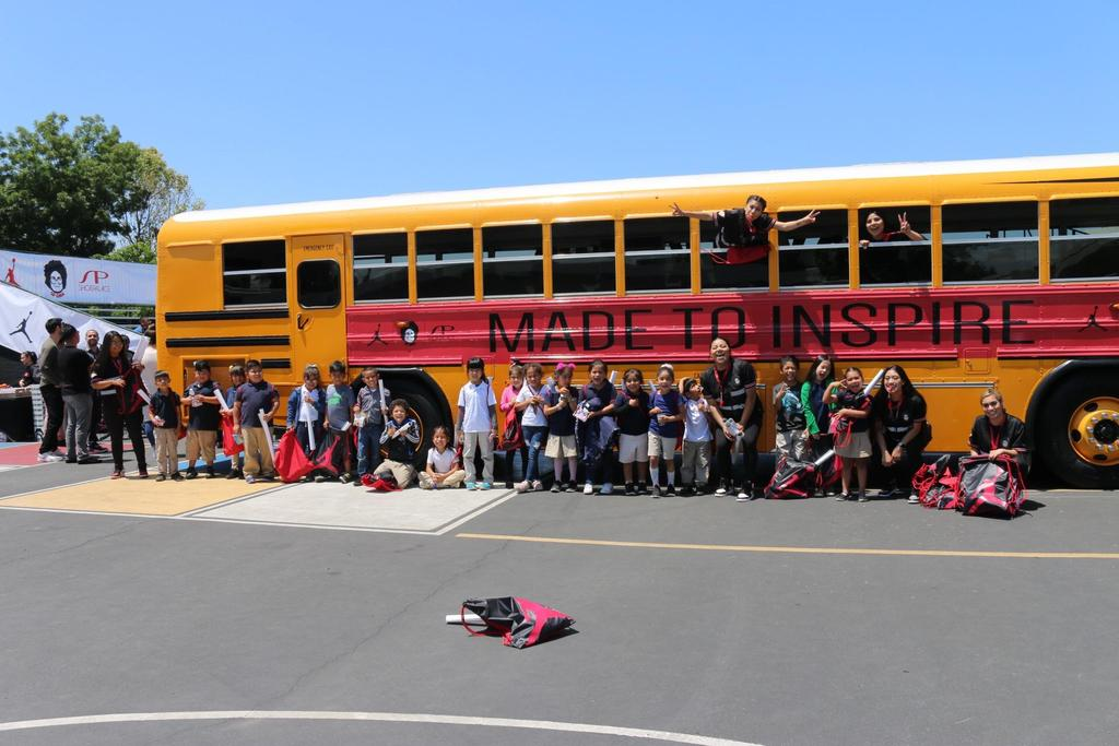 students stand in front of SP Gina decorated bus with Air Jordan backpacks in hand