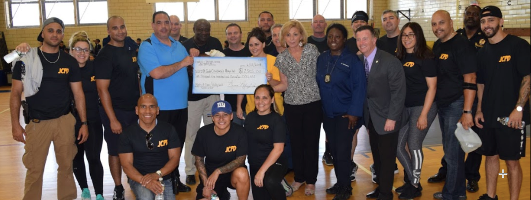 Students and teachers stand with the Jersey City Fire Department after a charity volleyball game