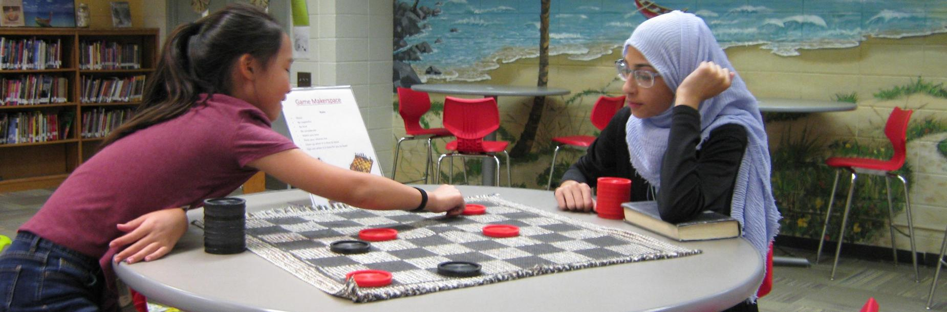 Students playing checkers in the learning commons makerspace