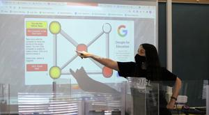 Seventh grade math teacher Jaclyn Manzo explains the digital version of Mancala, an ancient game from Eritrea and Ethiopia, to pre-algebra students during Cultural Diversity Day on May 21.