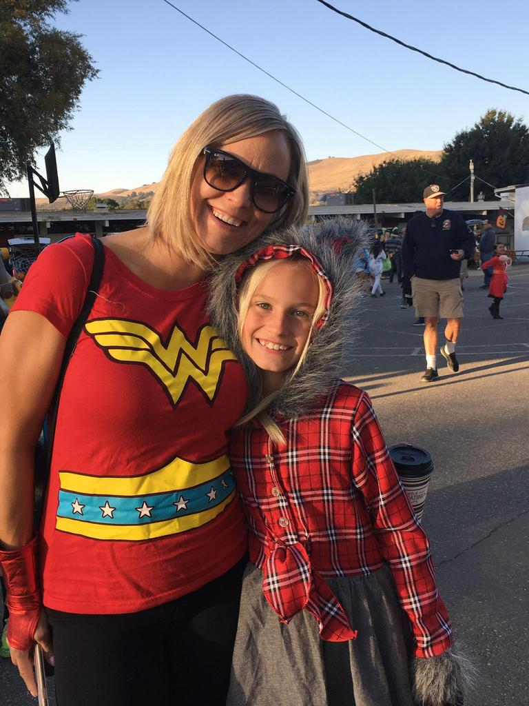 adult dressed in wonder woman costume and child in plaid shirt