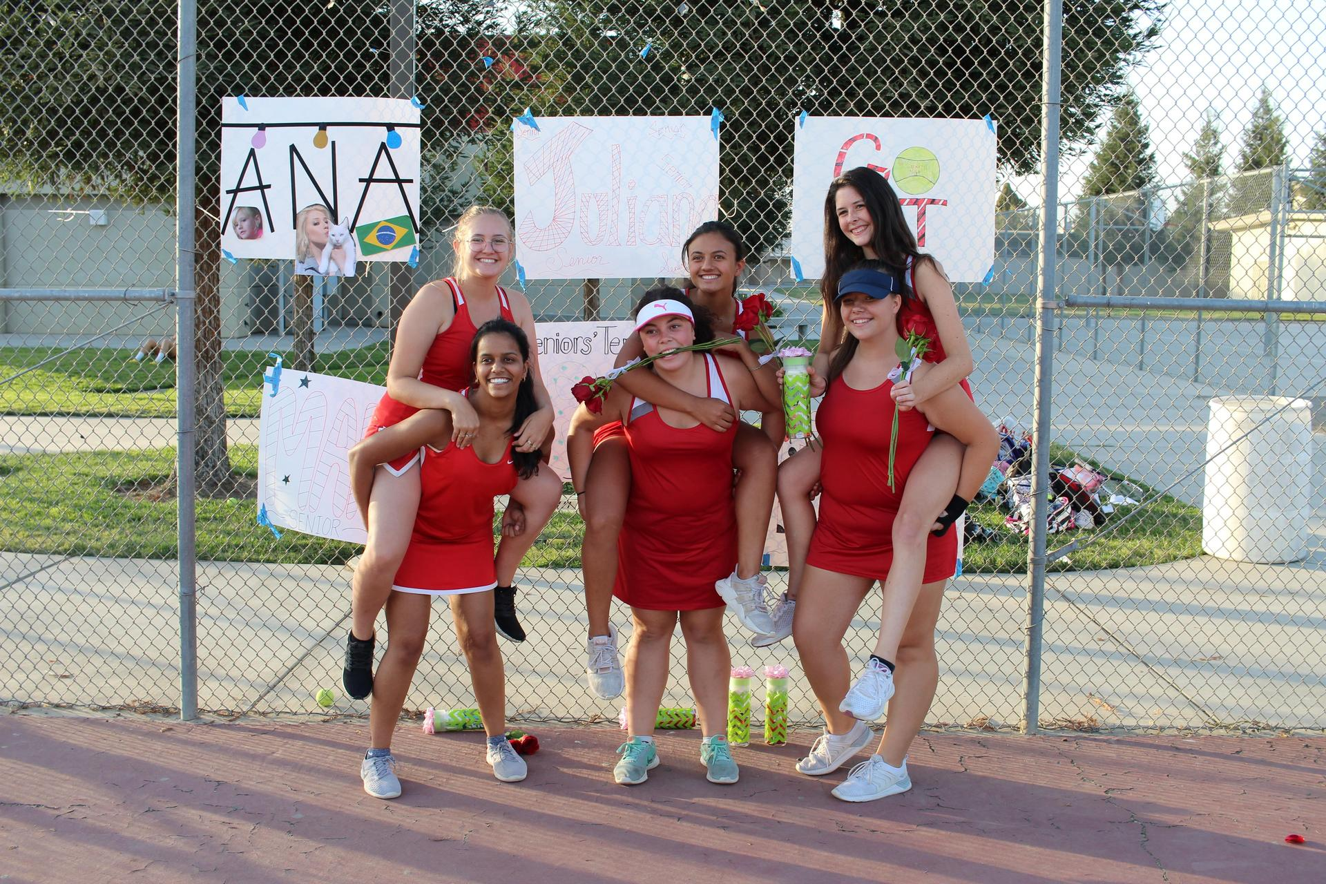 Senior tennis players posing at Senior Night.