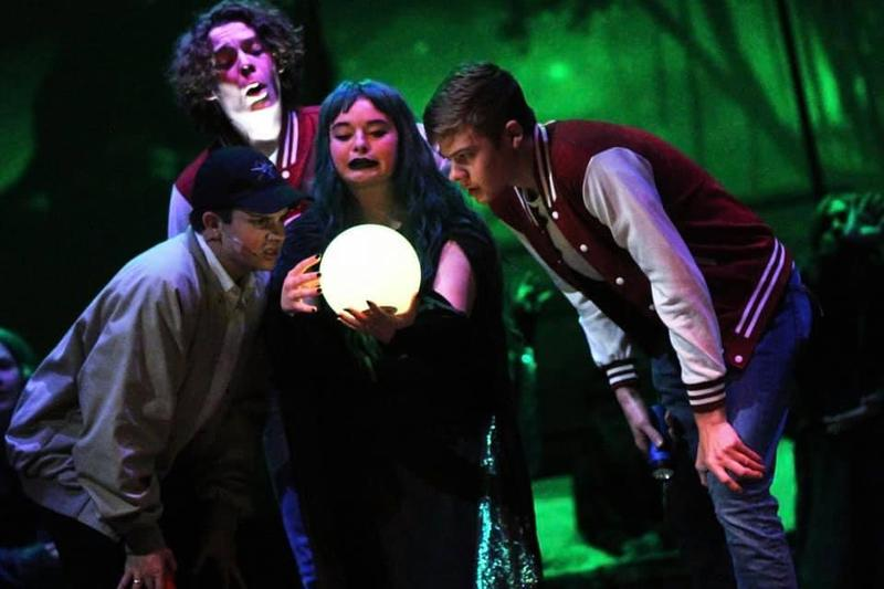 4 students in costume looking an illuminated ball