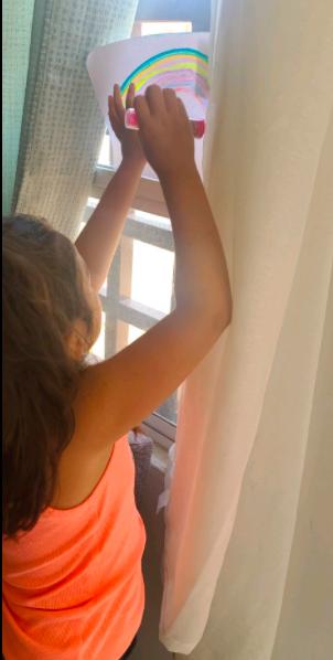Girl holding up rainbow drawing to window