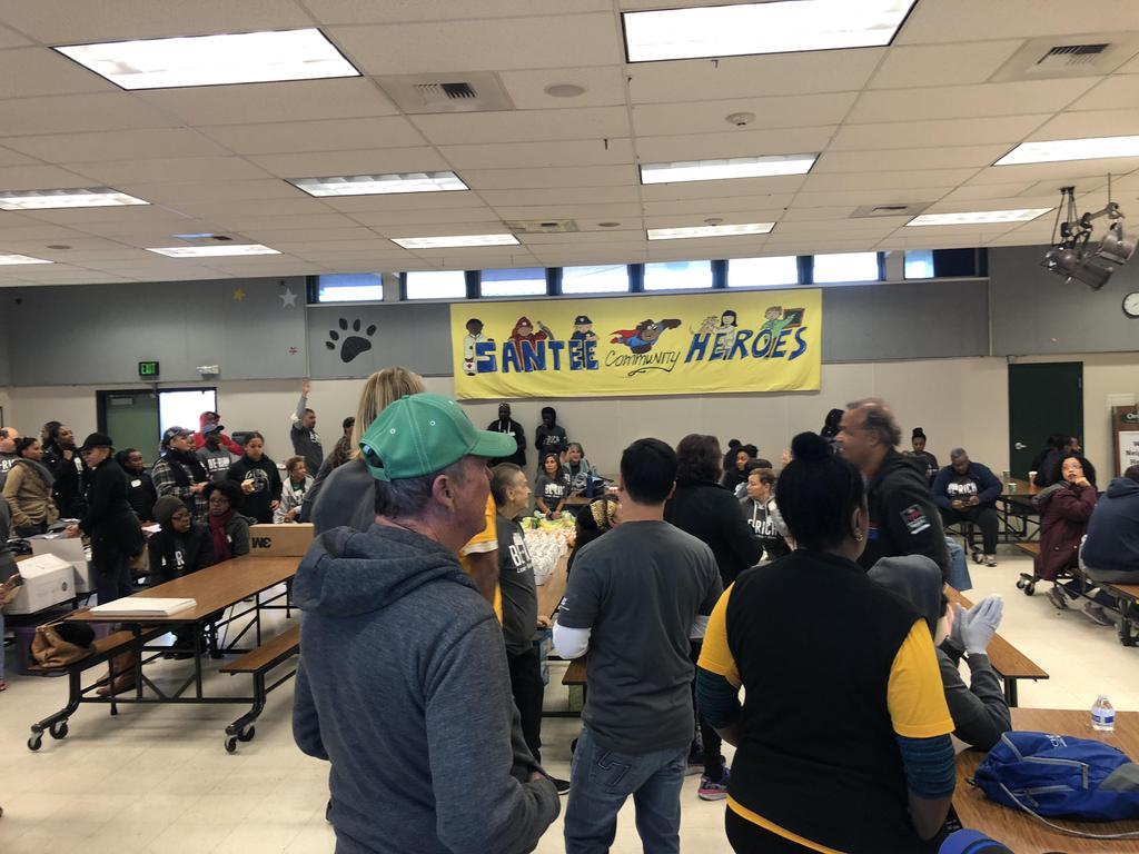 NBCC members in cafeteria standing beneath sign they donated year prior