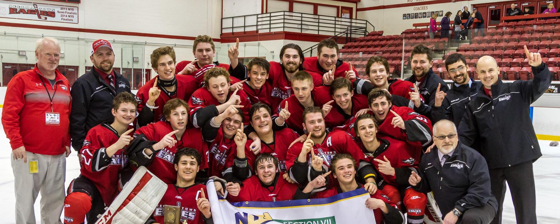 The Varsity Hockey Team right after winning, huddling around a banner all smiling and hold up their pointer finger to signify being the Number One team in their Championship