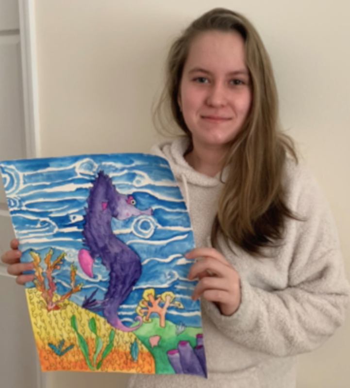 Student artist spotlight: student is holding up her artwork of a beautiful seahorse underwater. The drawing is vibrant and colorful.