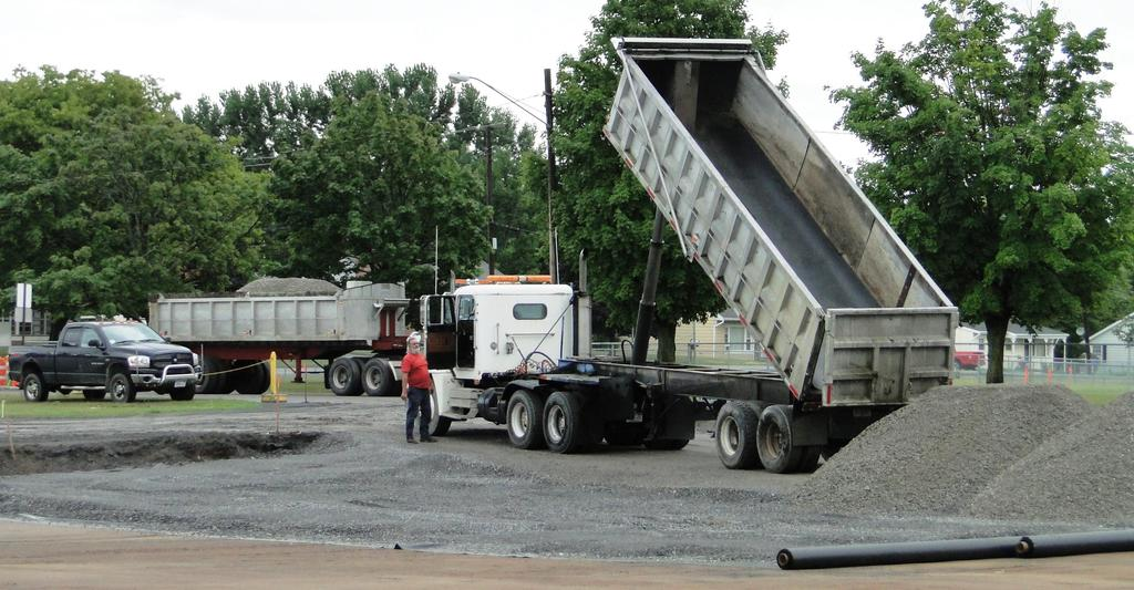 Two large dump trucks deliver stone that will be used to help construct the new bus loop