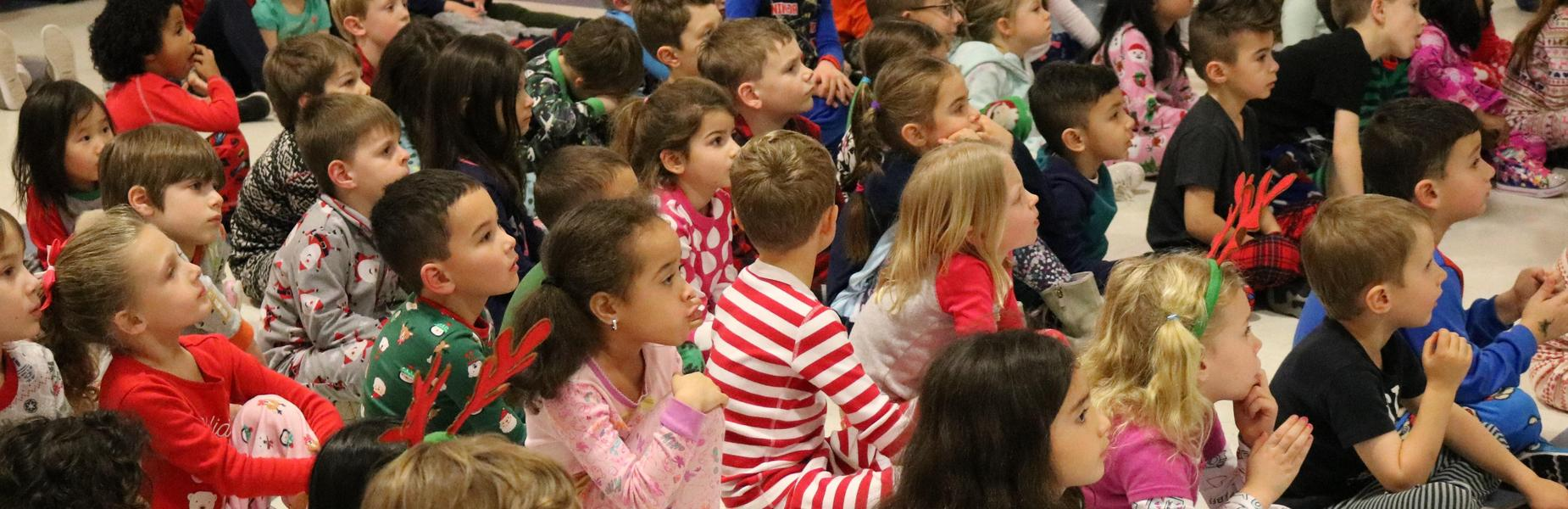 Lincoln kindergartners, dressed in pajamas, listen as principal Audrey Zavatz reads The Polar Express.