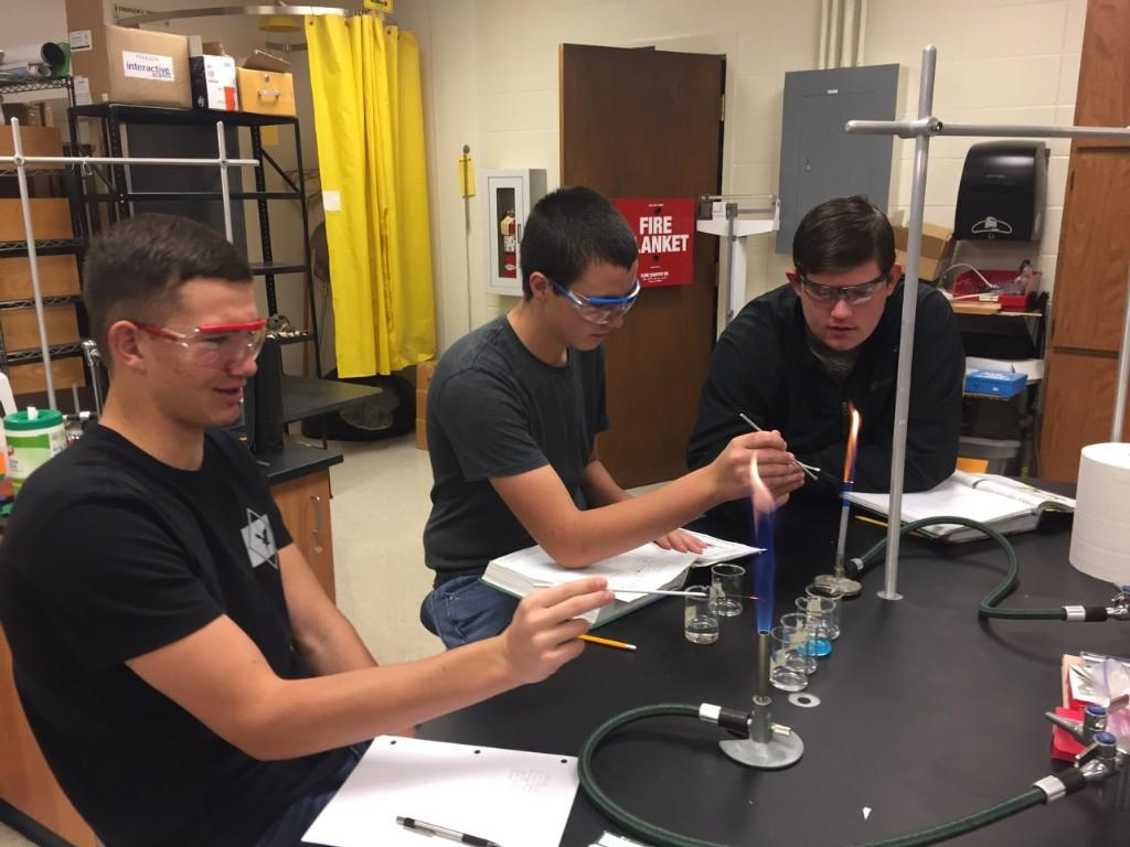 Three students doing a science experiment