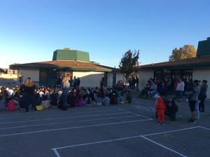 Parents and students gathered on blacktop for assembly, image 2
