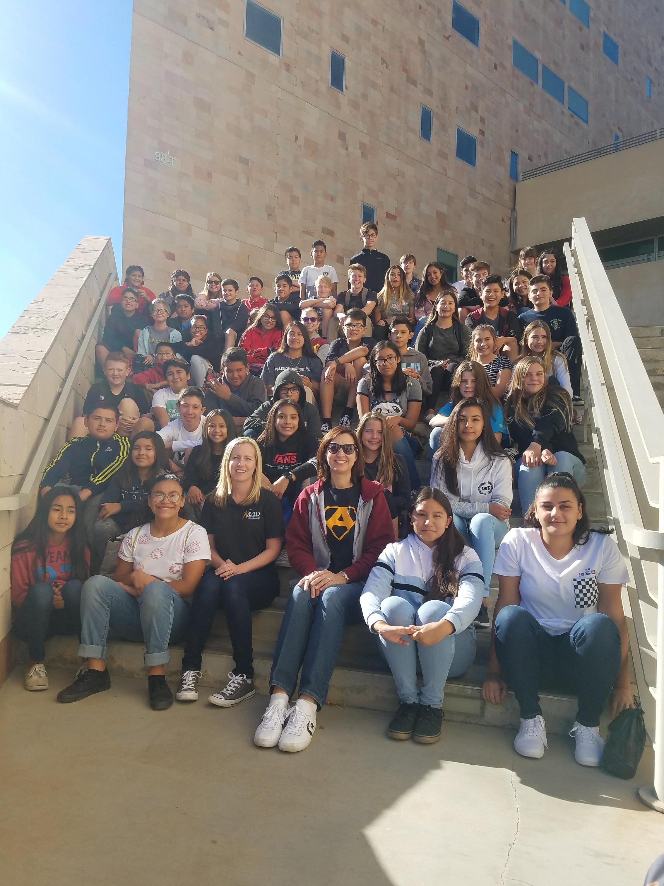 A large group photo of AVID students and their advisors, Mrs. Schultz and Mrs. Lapworth sitting on steps.