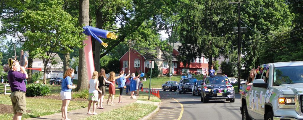 Photo of principal blowing horn and teachers and staff waving as 5th graders and families pass by during Grade 5 Clap Out Car Parade