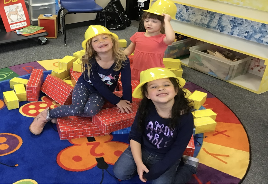 Three Early Childhood students playing with construction hats and blocks