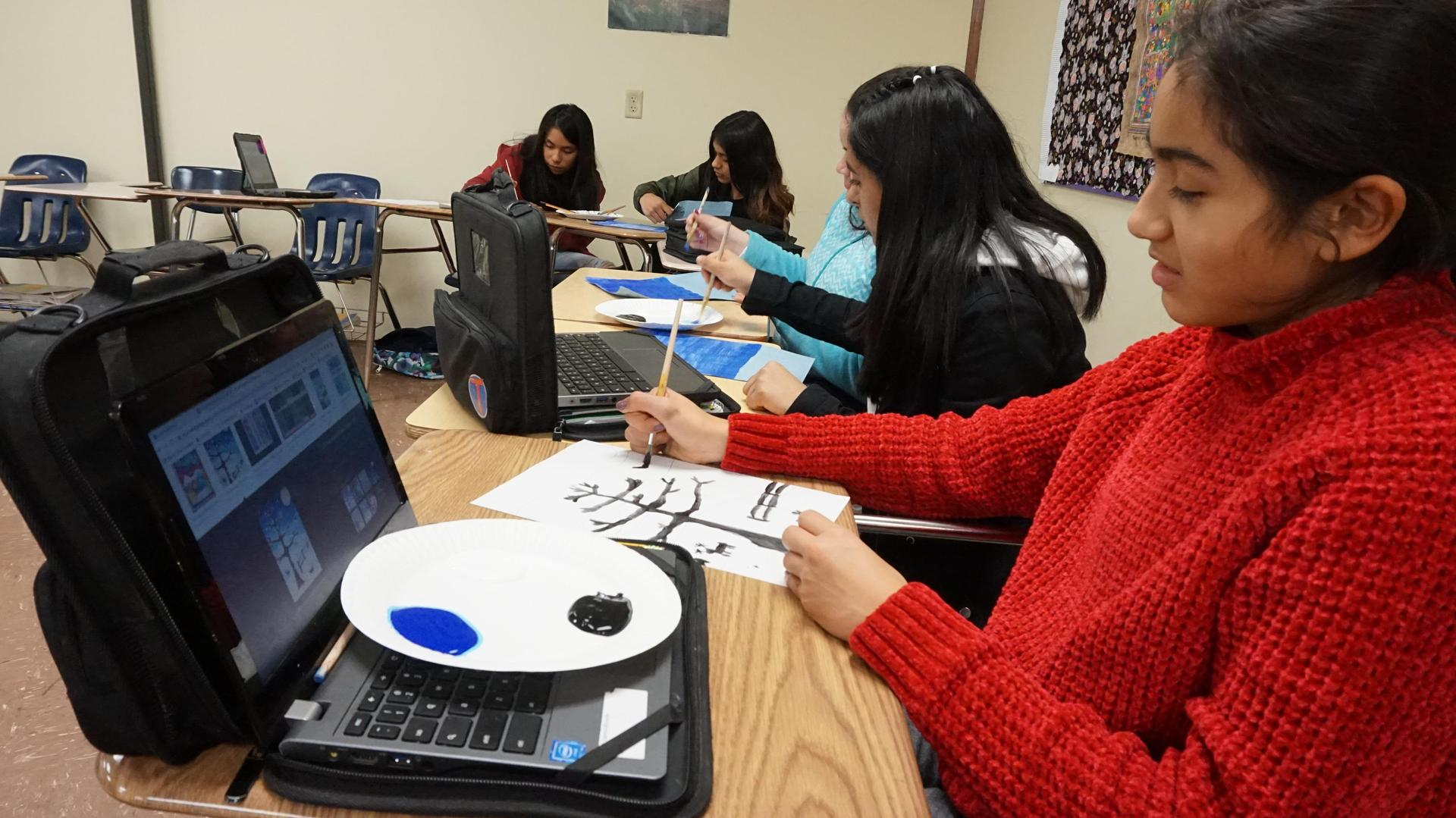 Female student using an image on her computer as an example for her painting