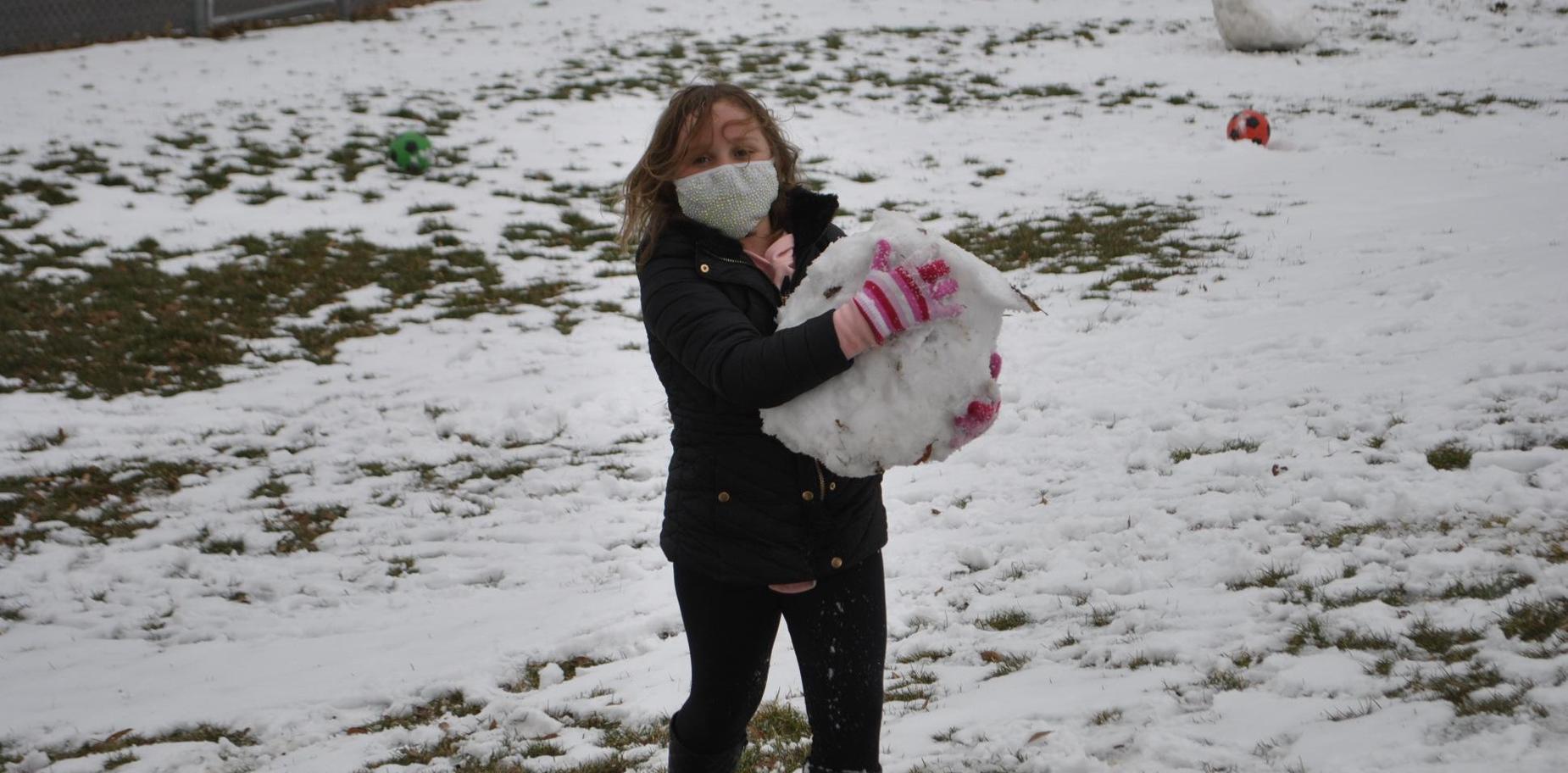 girl carrying snow ball