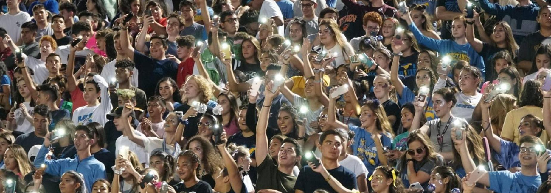 fans in the stands with cellphone lights on